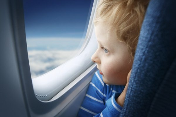 Curious little boy watching the sky through the airplane window. Shallow DOF. See more of this little boy: