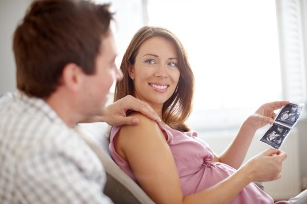 A beautiful pregnant woman looking at ultrasound scans with her husband - Copyspace