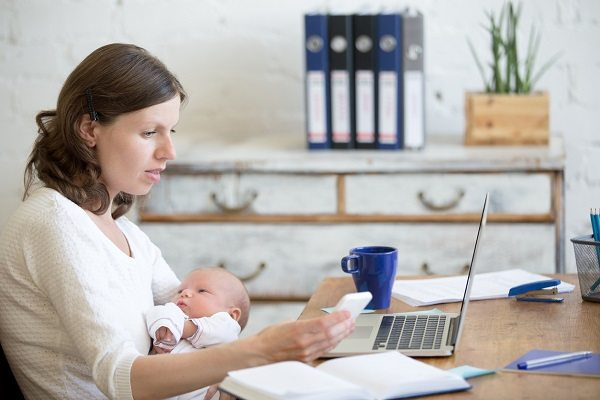 Portrait of young business mom holding her newborn cute babe while working in home office interior, looking at cellphone screen. Serious working mother using mobile phone and nursing new born child