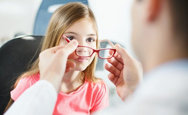 Little brow eyed girl visiting optician.She's having appointment for testing new glasses.Middle aged male optician is gently adjusting new frame and glasses on girl's face.